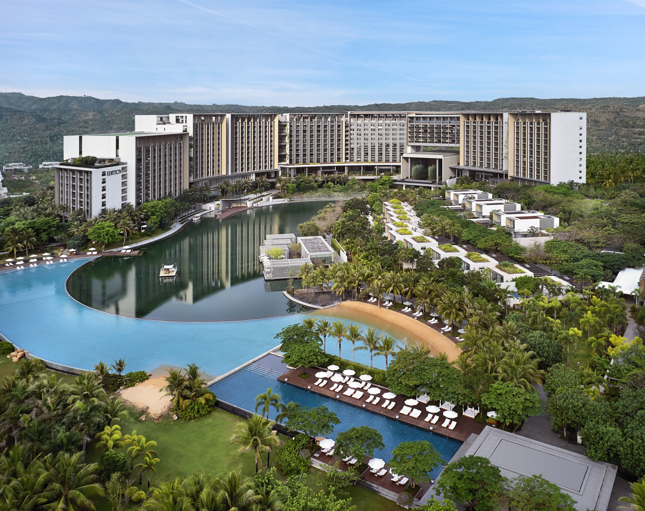 aerial photography of edition hotel in sanya showing blue pool with lounge chairs and hotel in background