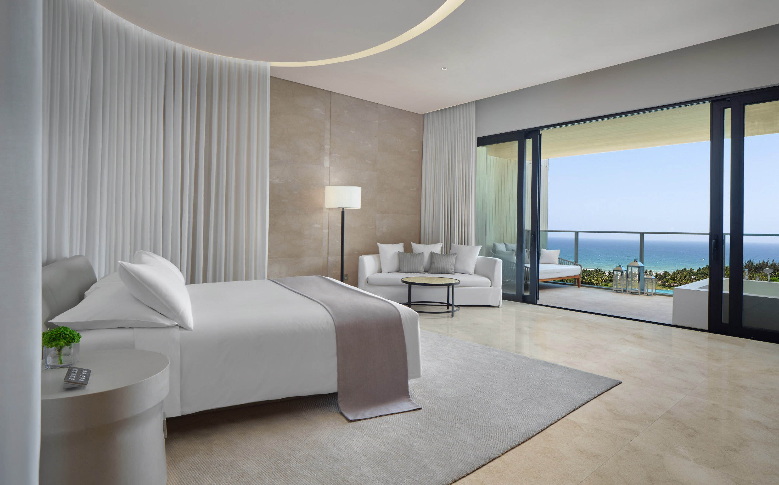 Loft hotel room showing bed with tan bed sash and white curtain and tan carpet. Sea view hotel room overlooking sanya bay at the edition sanya hotel.