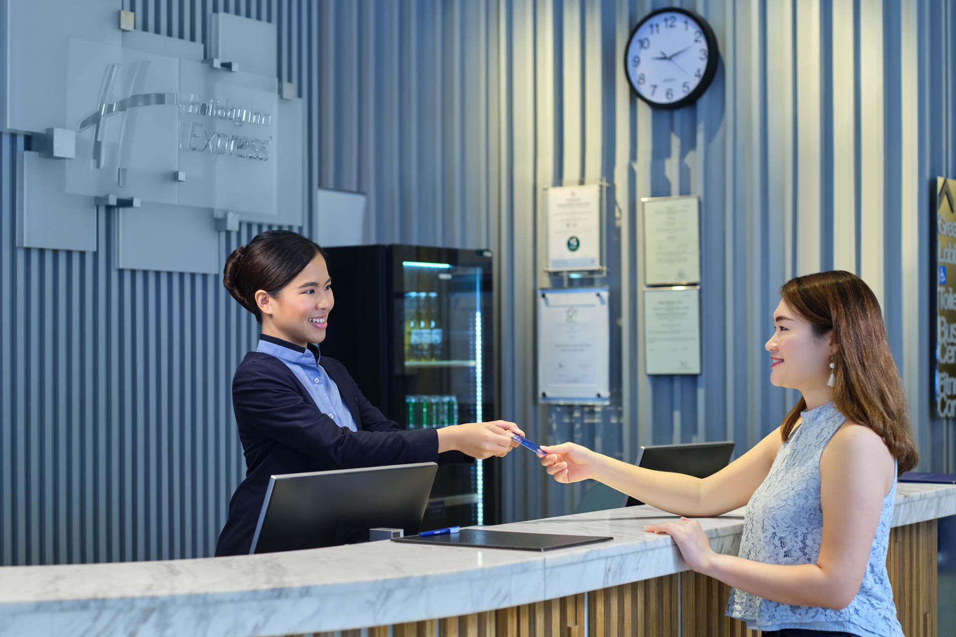 hotel front desk passing key card to hotel guest wearing blue at holiday inn express in singapore
