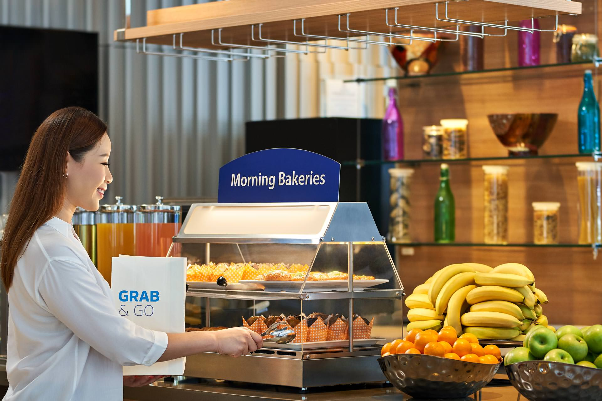 woman taking bread from hotel breakfast setup at holiday inn express in singapore