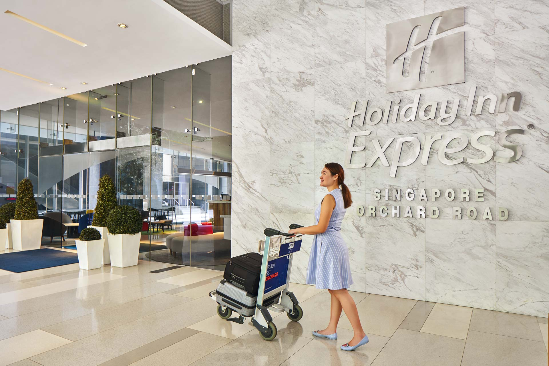 woman walking with luggage cart at the hotel entrace at holiday inn express in singapore