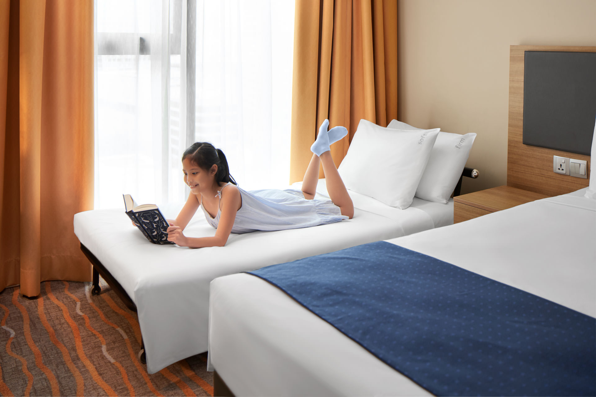 little girl reading a book on bed with blue dress at holiday inn express in singapore