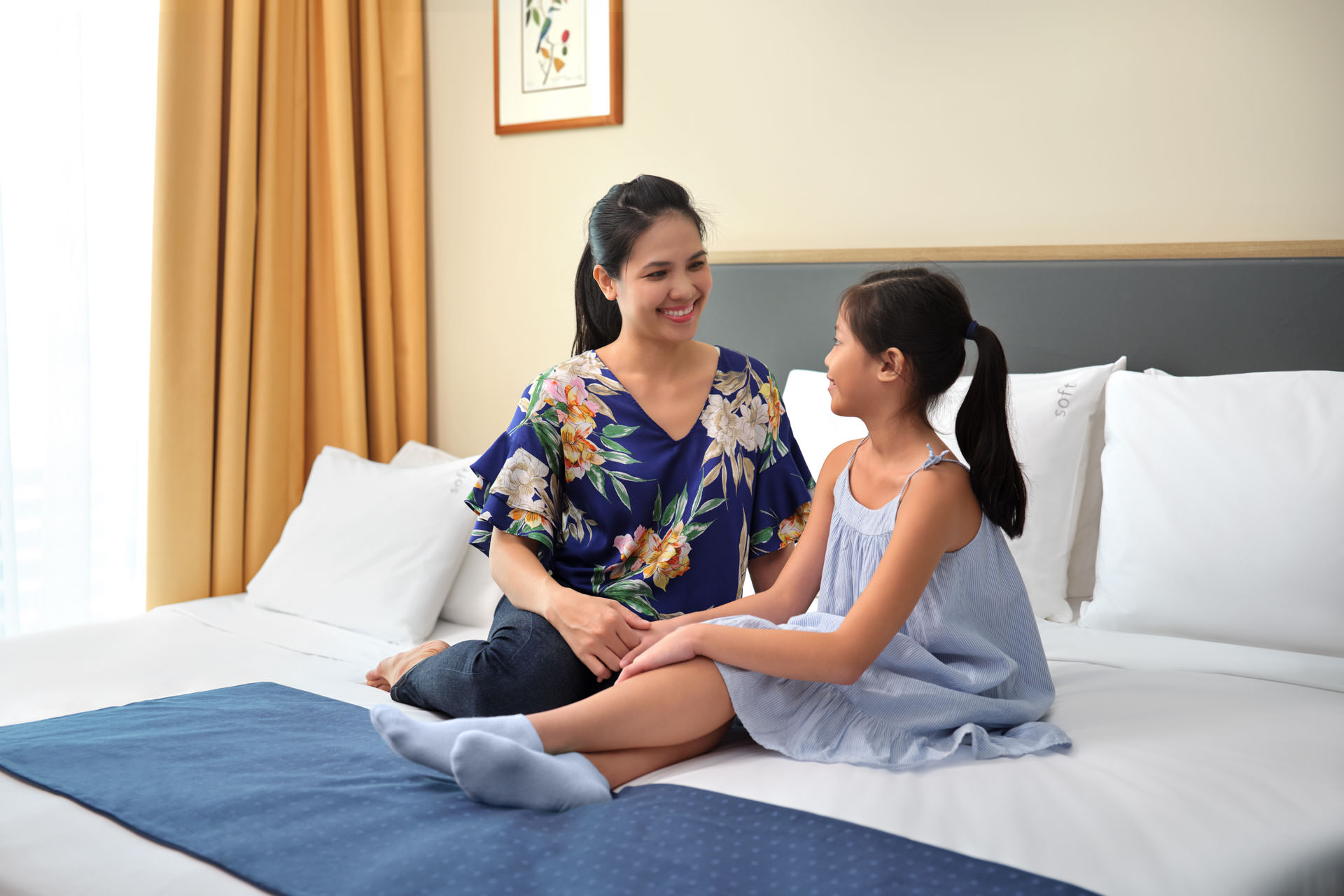 mother and daughter sitting on bed with blue bed sash and yellow curtains at holiday inn express in singapore