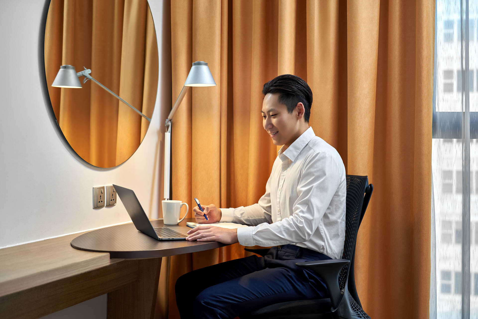 man sitting at hotel room desk with pen and computer at holiday inn express in singapore