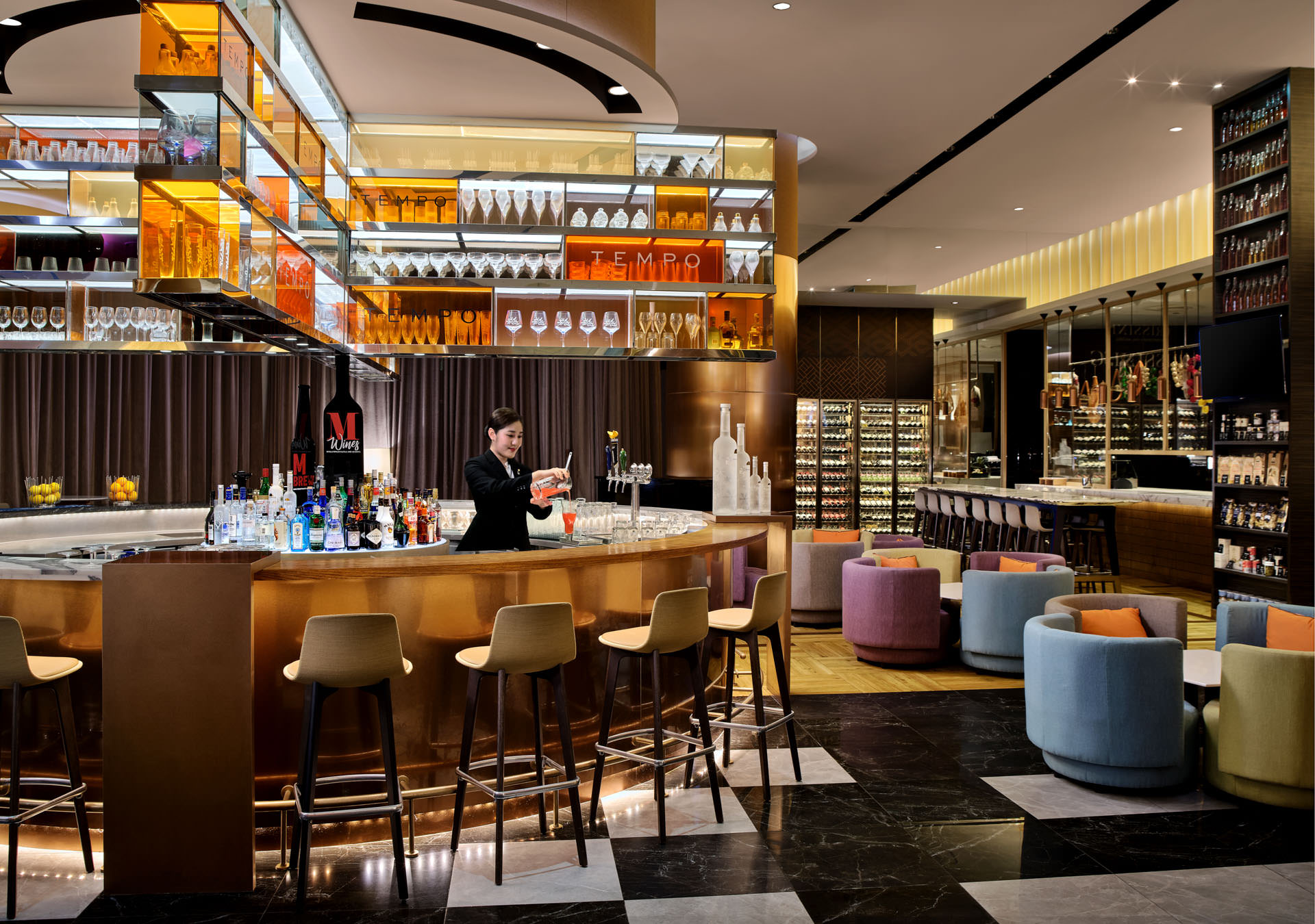 interior photography of tempo restaurant with colourful glasses on shelves and lounge area with sofas. Staff is pouring drink at grand copthorne waterfront hotel in singapore