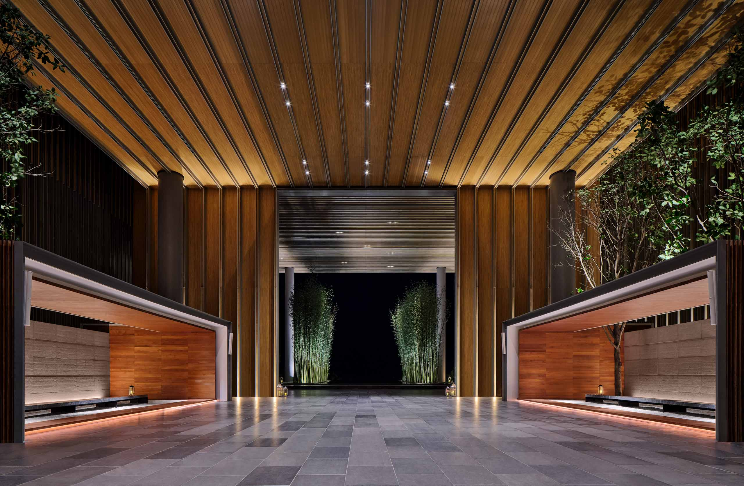 architectural photography of the main entrance at edition hotel in sanya china with wooden ceilings and concrete floor modern interior design