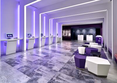 Hotel lobby at yotel in singapore wth kiosks and purple seats with purple carpet