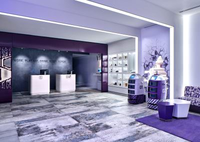 Hotel lobby with retail wall and check in desks and purple carpet and couch at yotel in singapore