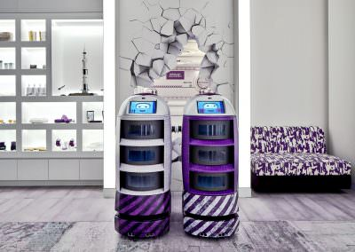 Hotel lobby with robots and retail wall with purple couch