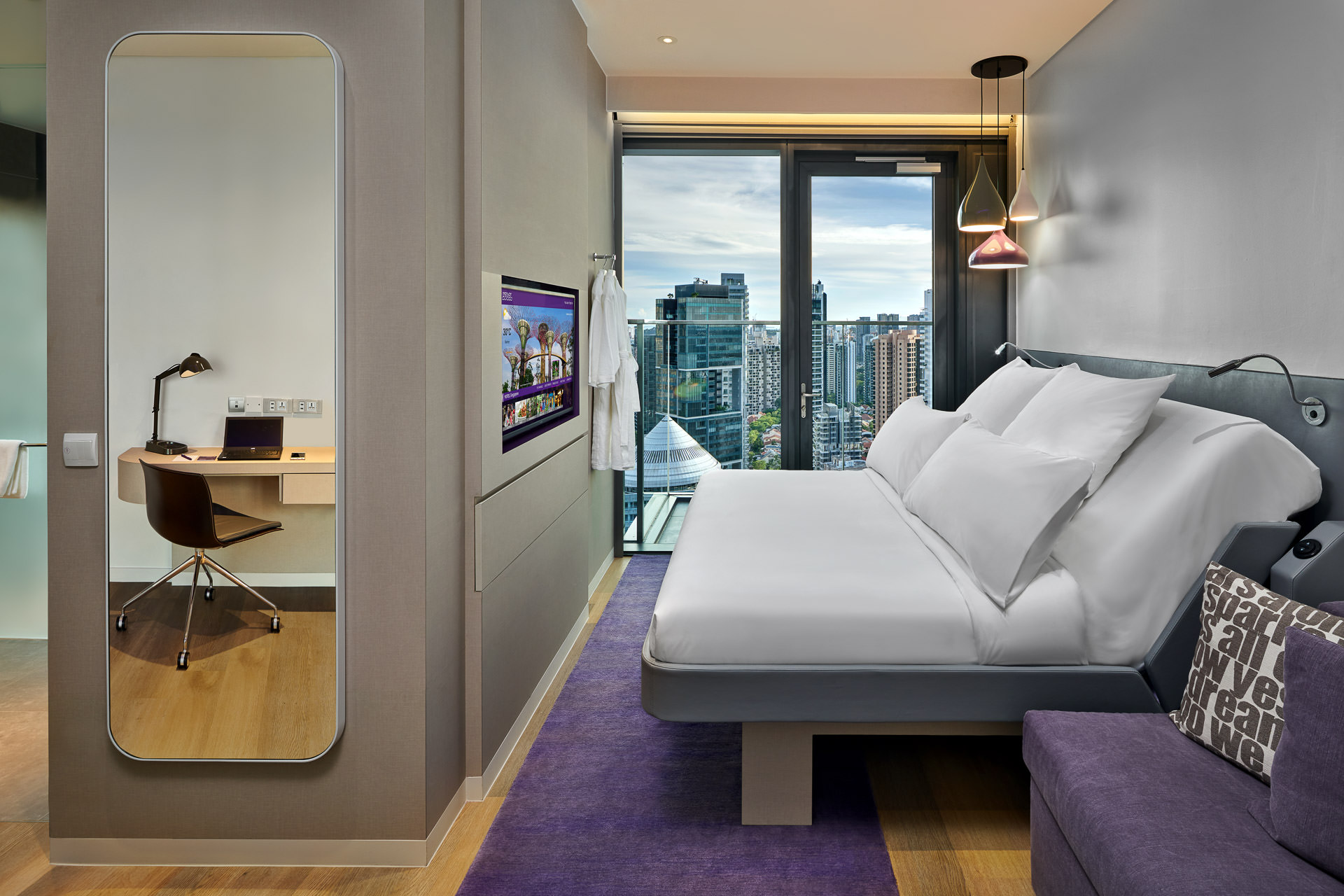interior photography at yotel in singapore of deluxe bedroom with mirror showing desk and laptop