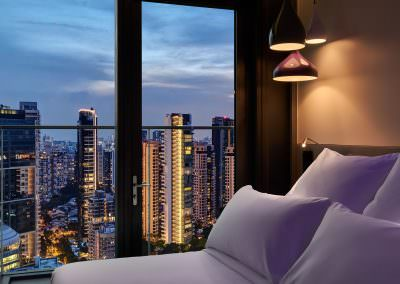 close up interior photography of bed at dusk overlooking singapore skyline with purple accent lighting