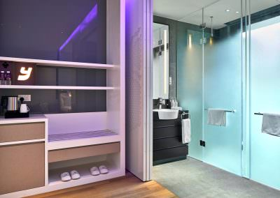 interior photography at yotel in singapore with deluxe bedroom bathroom with sink and shower