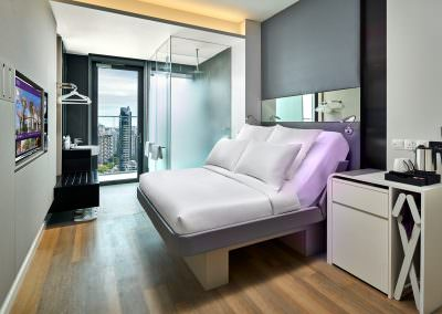 hotel Interior photography of the queen bedroom with balcony at yotel in singapore