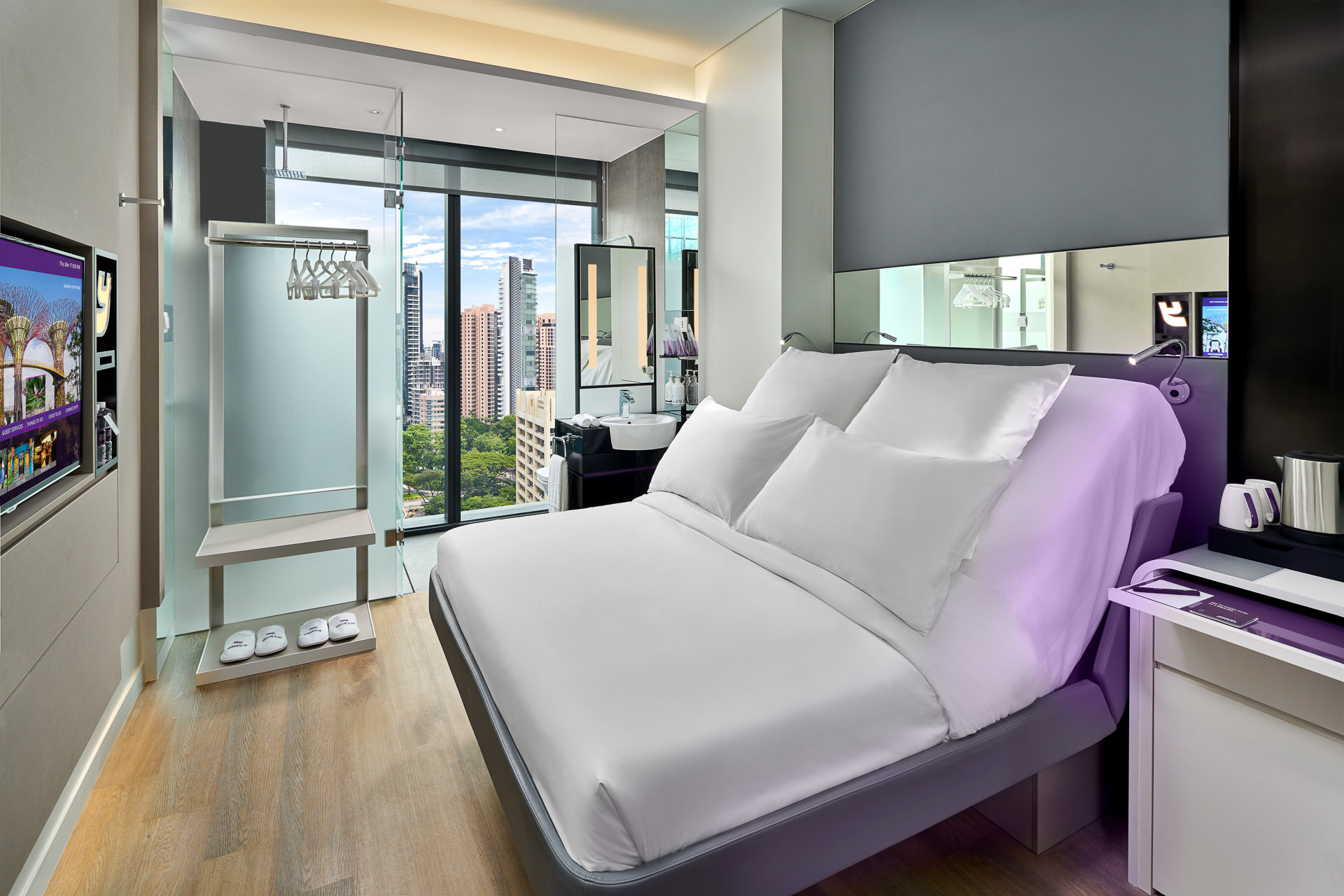 hotel interior photography of queen bed with view of singapore at Yotel