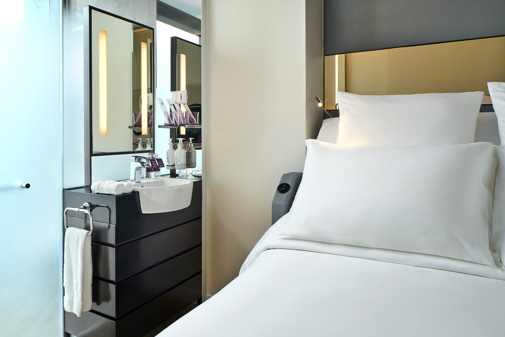 Interior photography at yotel in singapore close up of bed and bathroom setup with bathroom mirror and sink with accessories