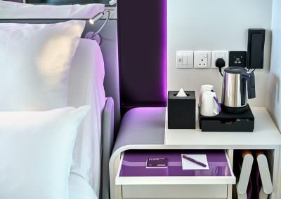 Detail photography of bedside table with purple accents, bedside light and coffee maker