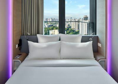 Close up photography of suite bedroom with purple accent lighting overlooking skyline of singapore