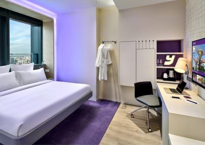 Hotel suite bedroom interior photography with purple lighting and skyline view of singpaore
