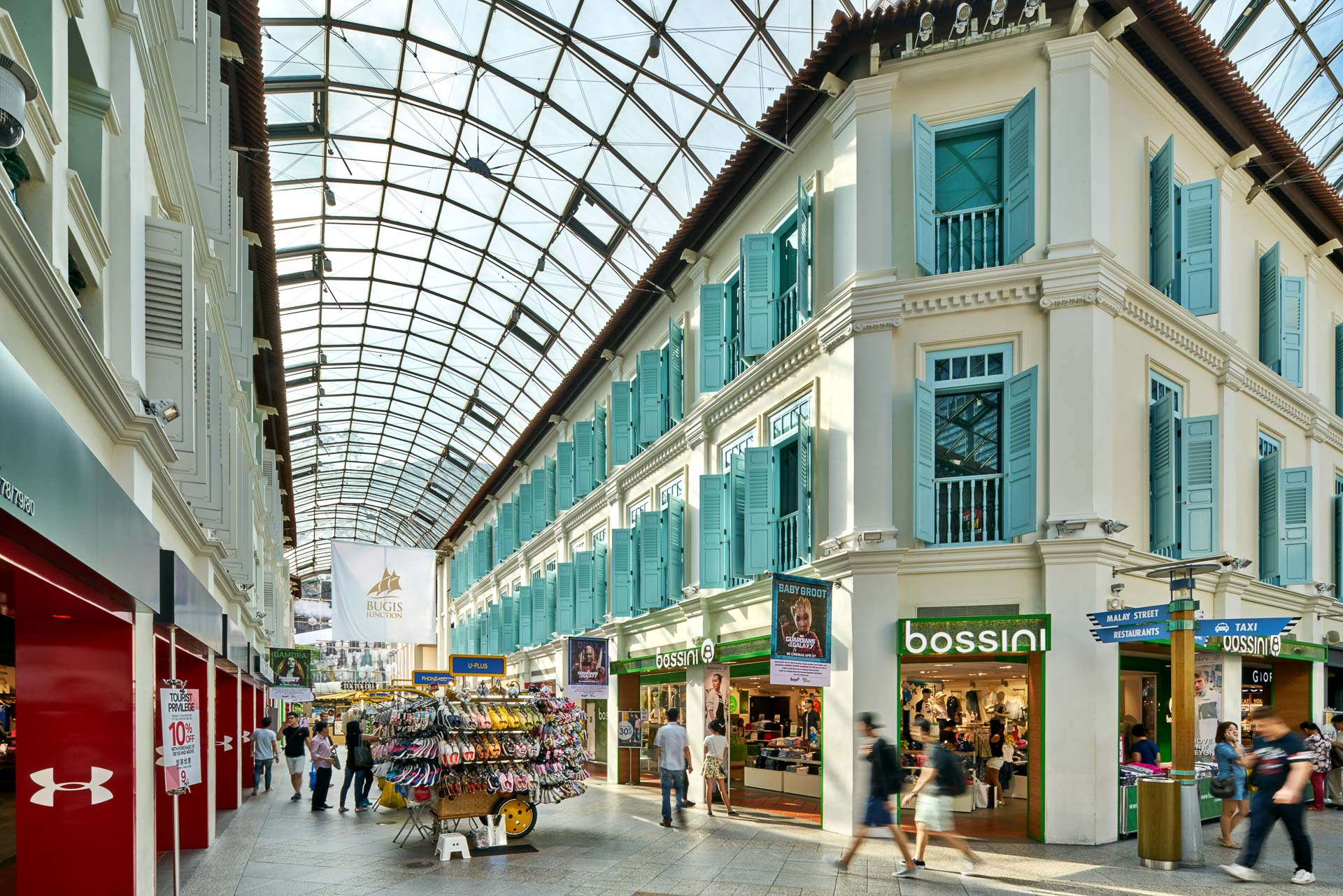 architectural photography of covered mall in singapore with shops and people walking