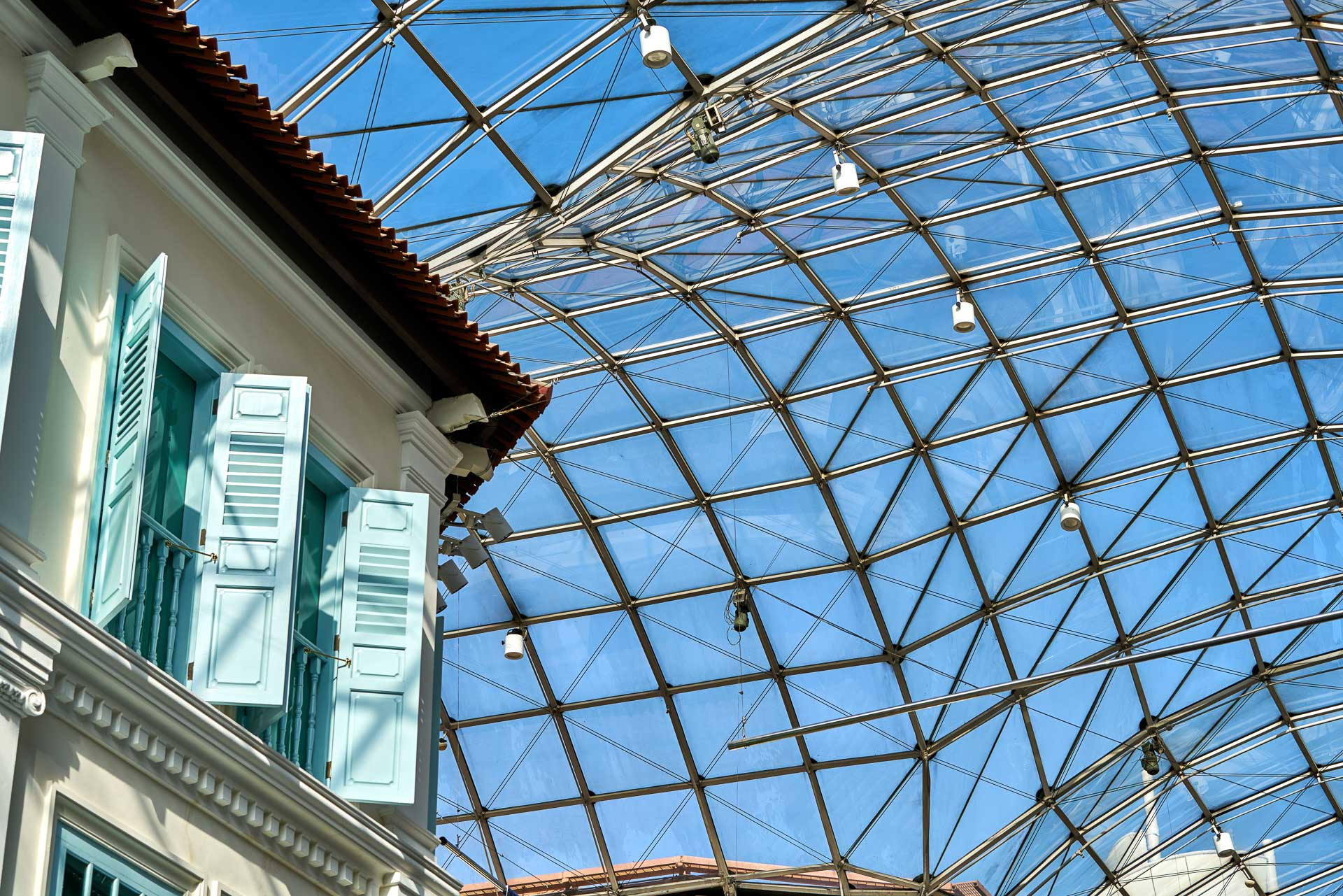 architectural photography of blue shutters and glass ceiling covering bugis junction mall in singapore