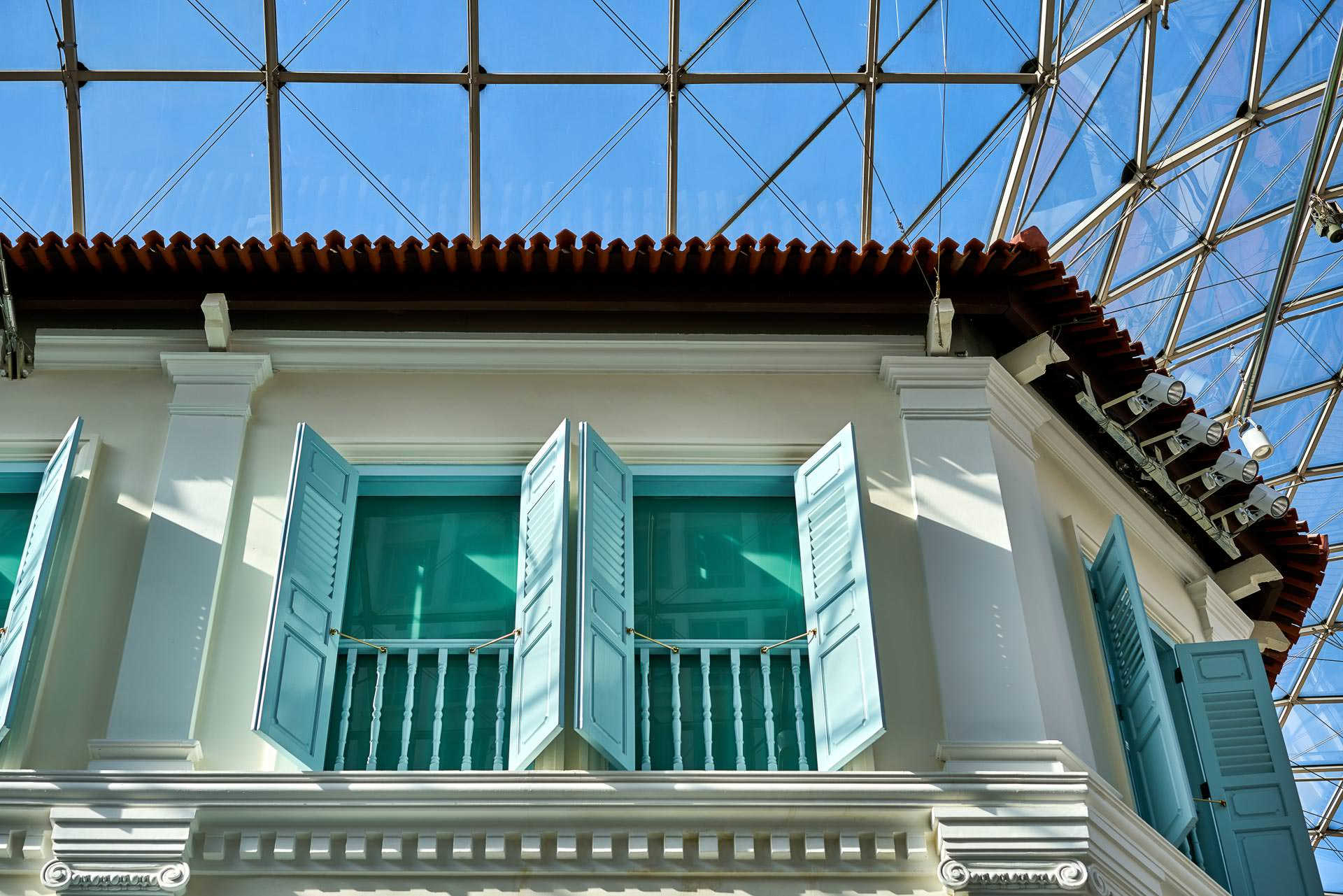 architectural photography focusing on blue shutters on a high floor under glass ceiling