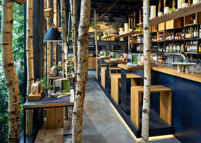 Interior photography of hans im gluck restaurant in singapore showing main restaurant area and bar with birch trees