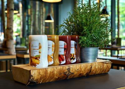 Product photography of the sauces at hans im gluck restaraunt in singapore on a wooden tray surrounded by greenery