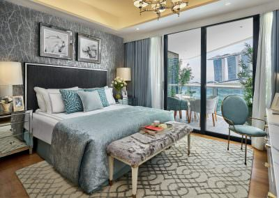 architectural interior photography of the second bedroom at marina bay suites in singapore with view of marina bay sands hotel and blue bedsheets and pillows