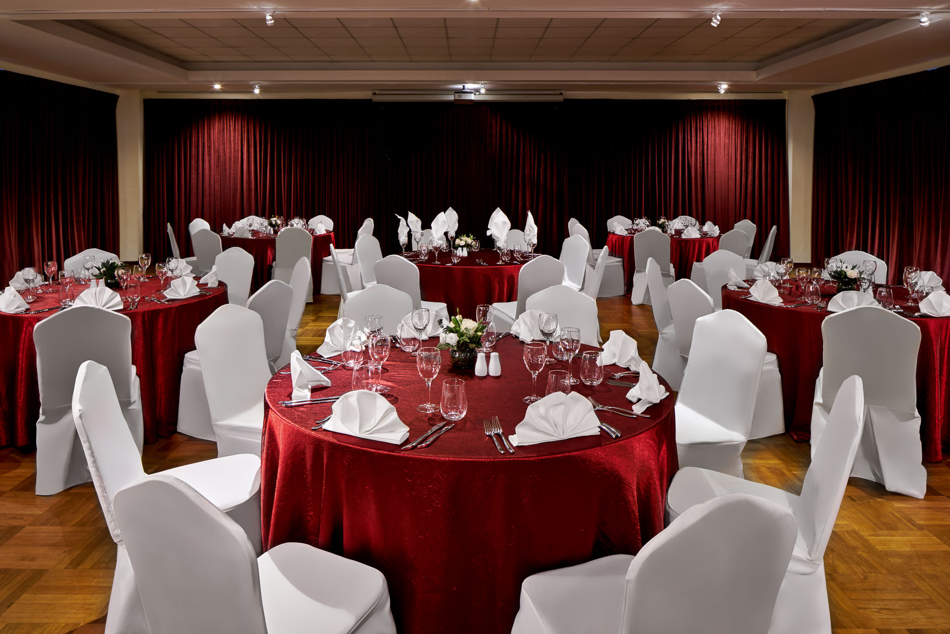 interior photography of a wedding setup with shimmering red tablecloths and white chairs at swiss club in singapore