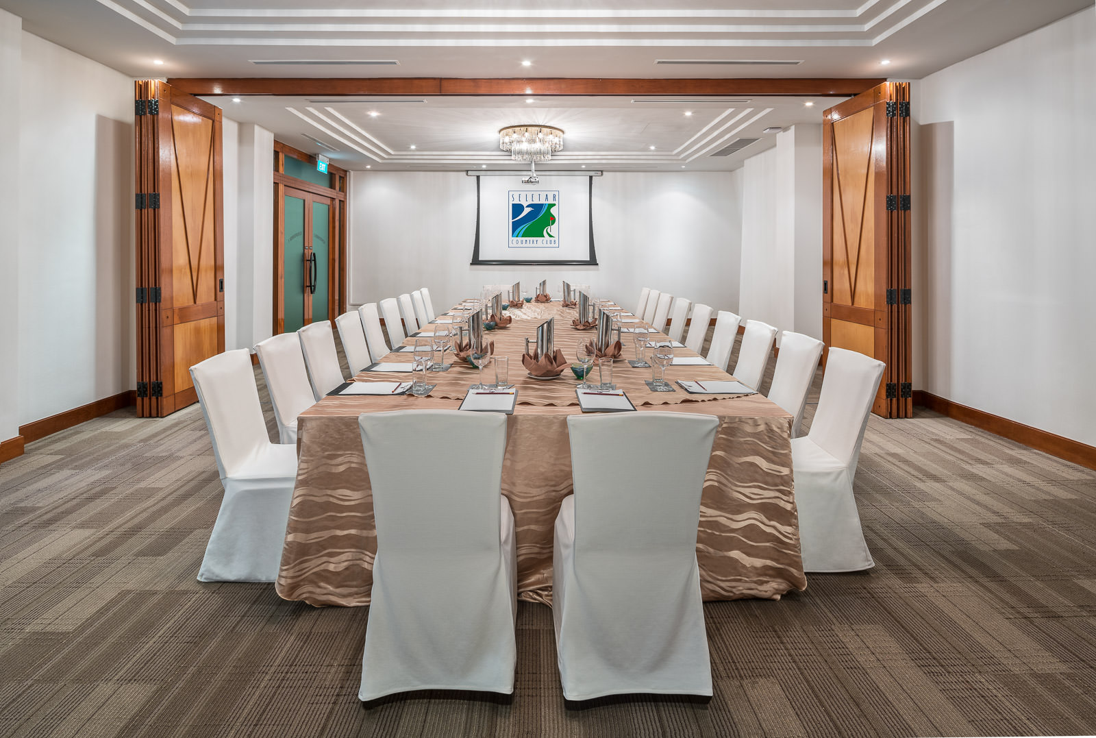 Interior photography of the seletar country club in singapore showing a meeting room with a long table and chairs with pitchers and projector