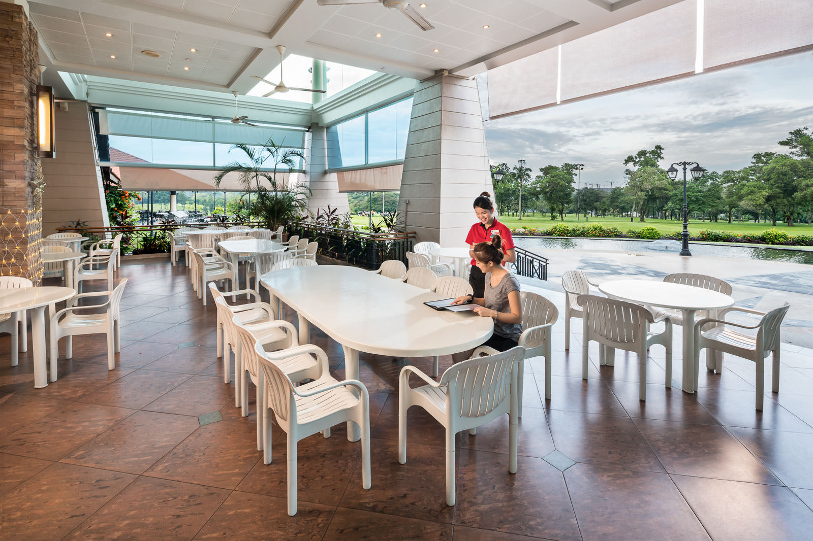 Interior photography of the seletar country club in singapore showing a waitress serving a client in the terrace restaurant