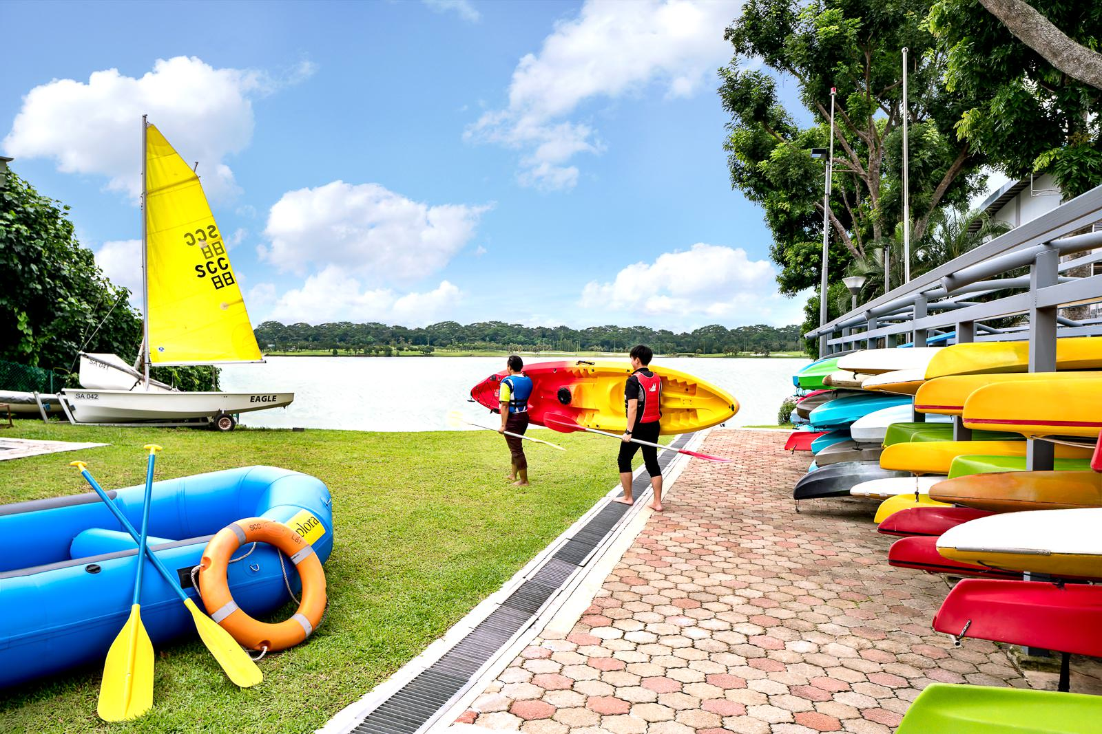 Interior photography of the seletar country club in singapore showing two men carrying a boat to the water with various water sports activities