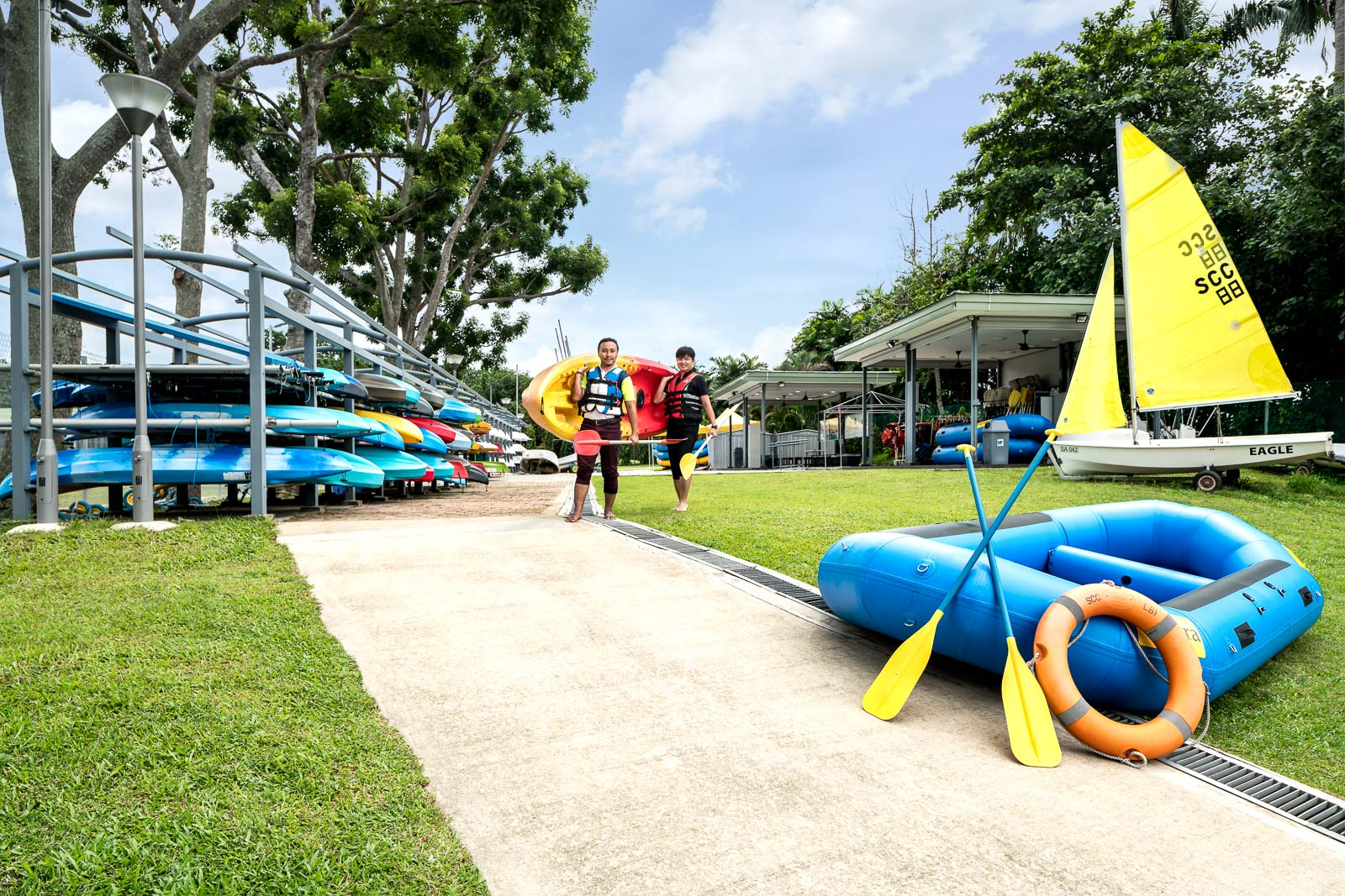 Interior photography of the seletar country club in singapore showing various water sports activities and two men carrying a boat to the water