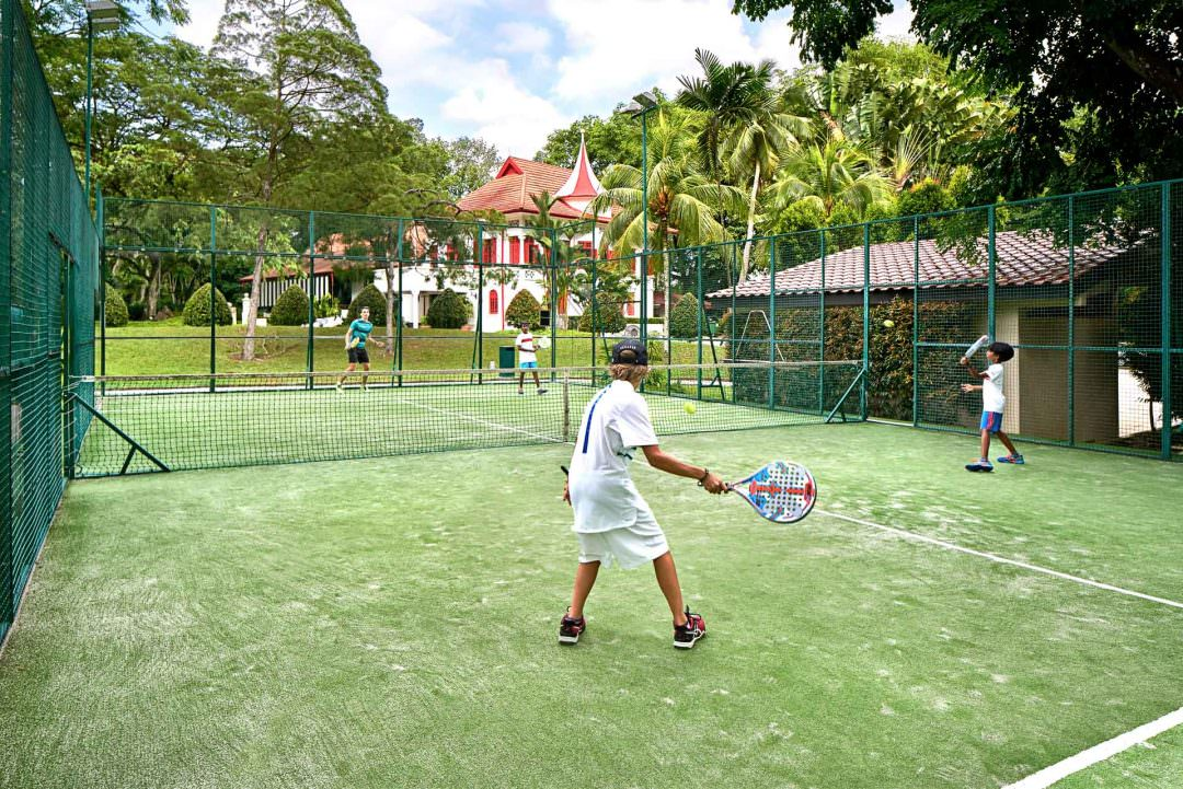 Lifestyle Photography with kids playing padel in outdoor padel court at swiss club singapore