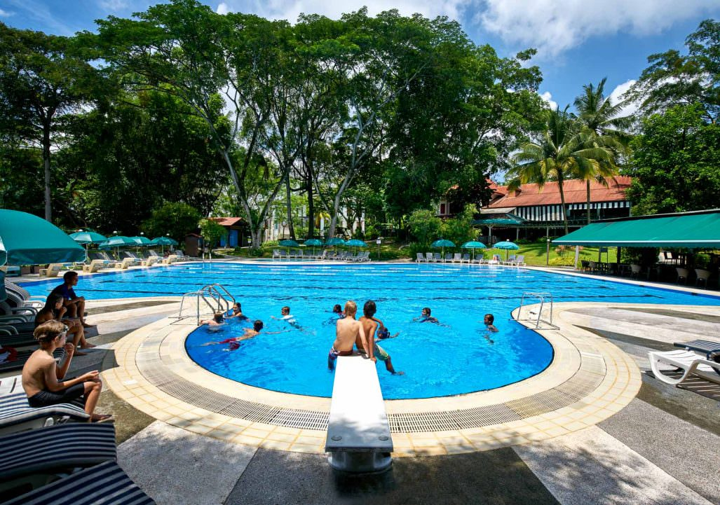 Lifestyle photography with kids playing at pool at swiss club singapore