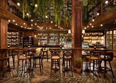 interior photography of the overview of the 3rd floor bar area with vintage chairs and tables with overhead plants and lights