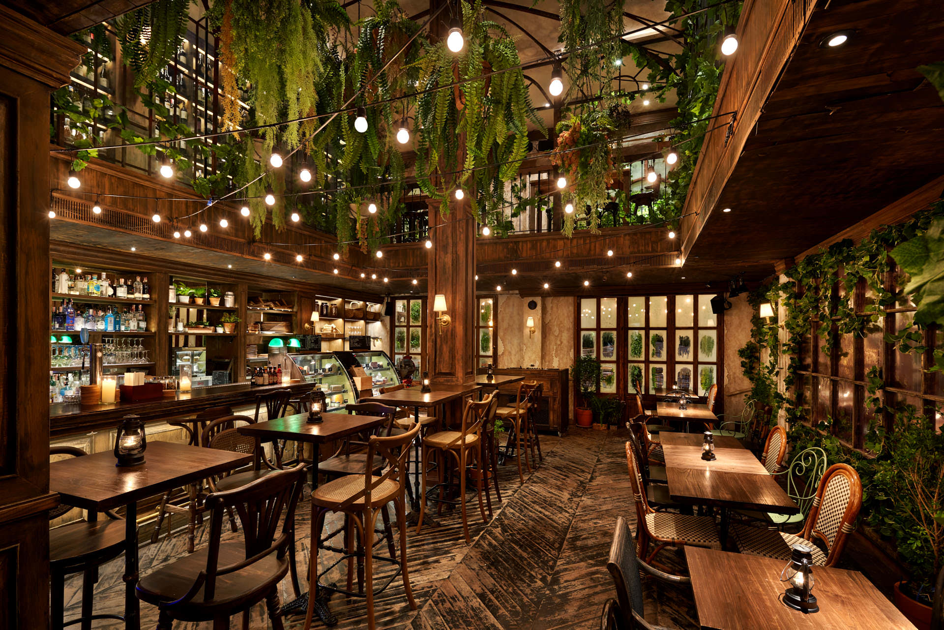 Architectural photography of the lower seating area showing vintage chairs and tables with green hanging plants above