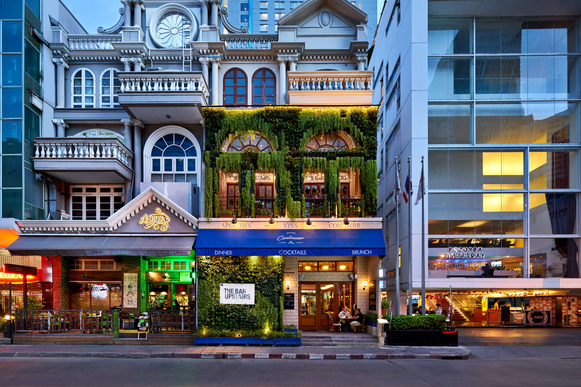 """Architectural photography of """"The Bar Upstairs"""" in bangkok with greenery covering the facade of the building."""