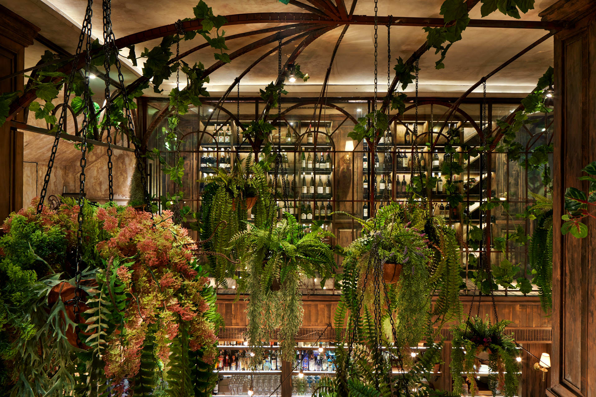 Interior design photography of the top atrium with iron beams supporting green plants above the lower seating area