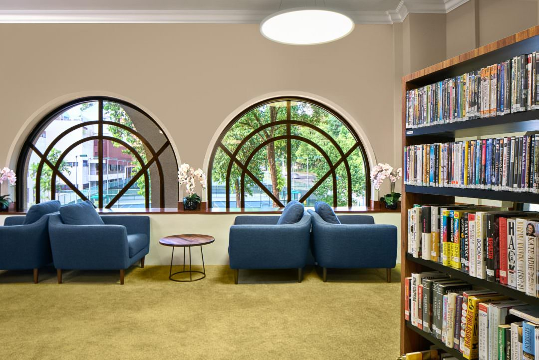interior photography of the library showing a study area and window view at tanglin club in singapore